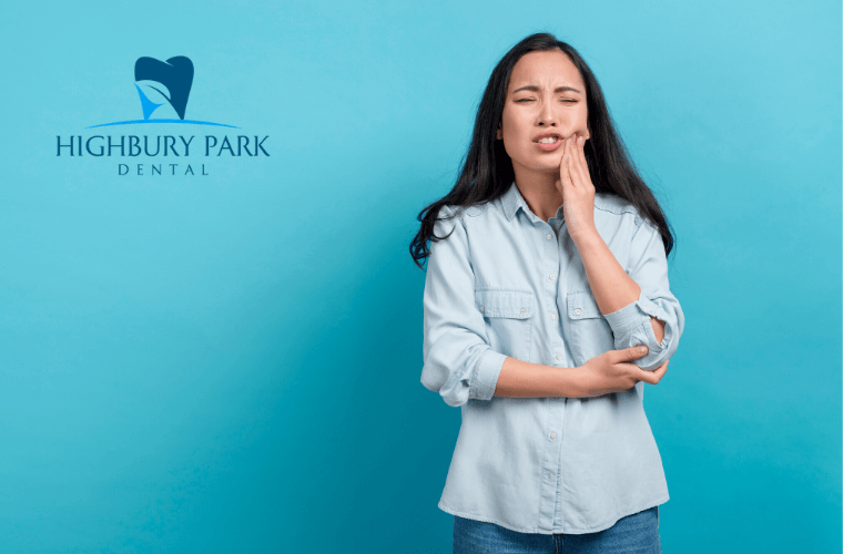 woman standing in front of blue backdrop holding her jaw in pain