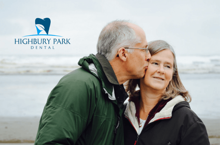 Senior couple at the beach on a cool day, man kisses his wife on the cheek