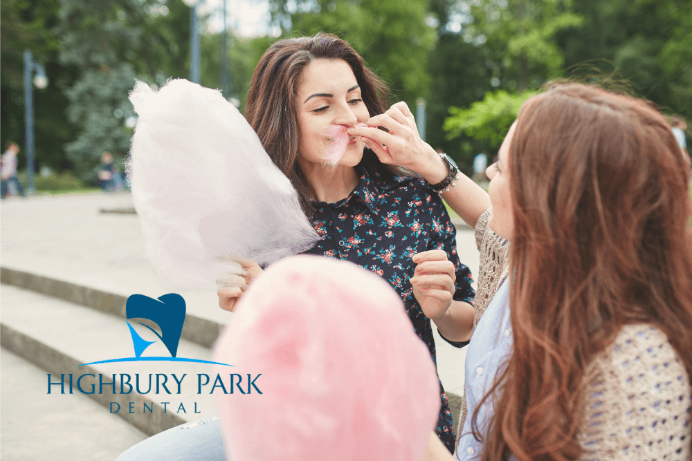 two woman sit on stairs in the park and eat pink cotton candy